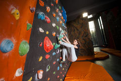 Сильный женский альпинист на стене валуна взбираясь крытой Стоковое Фото