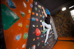 Сильный женский альпинист на стене валуна взбираясь крытой Стоковые Изображения