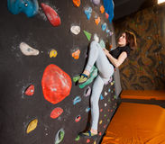 Сильный женский альпинист на стене валуна взбираясь крытой Стоковая Фотография RF