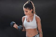 Сильный и мышечный женский работать с гантелью Стоковое фото RF