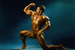 Сильный мышечный культурист человека показывает его мышцы Стоковое Изображение