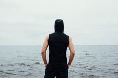 Сильный человек фитнеса yang представляет на пляже около моря и утесов Стоковые Изображения