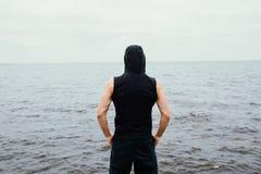 Сильный человек фитнеса yang представляет на пляже около моря и утесов Стоковое Фото