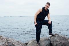 Сильный человек фитнеса yang представляет на пляже около моря и утесов Стоковые Изображения RF