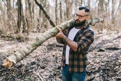Сильный lumberjack работая в лесе Стоковые Изображения RF