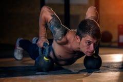 Сильный sporty делать человека нажимает вверх с колоколом чайника Стоковое фото RF