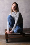 Сидя девушка представляя на палубе Серая предпосылка Стоковое фото RF