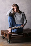 Сидя девушка с книгой Серая предпосылка Стоковая Фотография