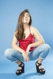 Сидя на корточках девушка смотря вверх Стоковые Фото