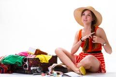 Сидя чемодан девушки близко переполненный Стоковая Фотография