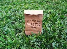 Скажите нет к хозяйственной сумке полиэтиленовых пакетов экологической на зеленой траве стоковое изображение rf