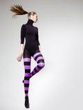 Скакать женщины одел в пурпуровых striped колготках и черной верхней части - скопируйте космос Стоковые Фото