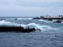 Скакать молодого человека конкретной пристани в море с волнами максимума и прибоя в puerto de Ла cruz Тенерифе Стоковые Фото