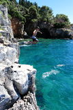 Скакать от скалы в океане Стоковое Фото