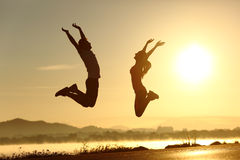 Скакать пар фитнеса счастливый на заходе солнца