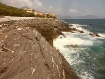 Скала и волны разбивая на ей в морях Генуи стоковое изображение