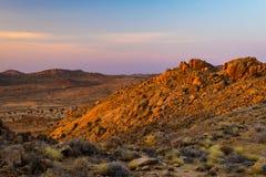 Скалистая пустыня на сумраке, красочном заходе солнца над пустыней Namib, Намибии, Африке, накаляя утесах и каньоне Стоковые Фото