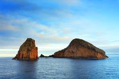 Скалистые образования в область Атлантическом океане, Азорских островах, увиденная от корабля на заходе солнца Стоковые Фото