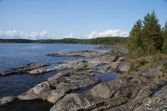 Скалистый скалистый берег озера, на береге сосны, мох Ясный солнечный день стоковое изображение
