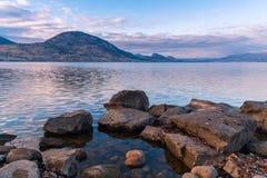 Скалистый бечевник с видом на озеро и горы на заходе солнца стоковые изображения rf