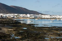 Скалистый пляж и Белые Дома в острове Graciosa Ла Caleta del Sebo стоковое фото