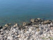 Скалистый пляж штиля на море стоковое изображение rf