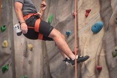 Скалолазание молодого человека практикуя на искусственной стене внутри помещения Стоковые Фотографии RF
