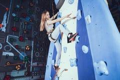 Скалолазание молодой женщины практикуя на стене утеса внутри помещения стоковое фото rf
