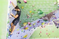 Скалолазание человека практикуя на искусственной стене внутри помещения актеров иллюстрация штока