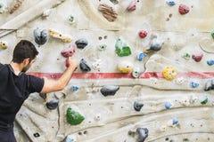Скалолазание человека практикуя на искусственной стене внутри помещения актеров стоковые изображения rf