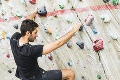Скалолазание человека практикуя на искусственной стене внутри помещения актеров стоковое изображение rf