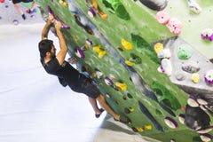 Скалолазание человека практикуя на искусственной стене внутри помещения актеров стоковое фото rf