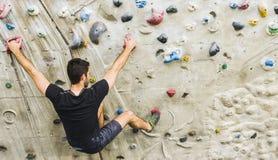 Скалолазание человека практикуя на искусственной стене внутри помещения актеров стоковое изображение