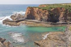 Скалы, шлюпка и волны в Порту das Barcas, Zambujeira повреждают Стоковая Фотография