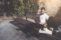 Скамейка в парке города человека фото сидя и отправляя СМС тетрадь сообщения Используя беспроволочный интернет Изучать в универси Стоковое Изображение