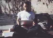 Скамейка в парке города человека фото сидя и отправляя СМС тетрадь сообщения Используя беспроволочный интернет Изучать в универси Стоковые Фотографии RF