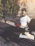 Скамейка в парке города человека фото сидя и отправляя СМС тетрадь сообщения Используя беспроволочный интернет Изучать в универси Стоковая Фотография