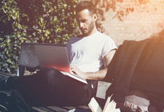 Скамейка в парке города человека фото сидя и отправляя СМС тетрадь сообщения Используя беспроволочный интернет Изучать в универси Стоковое фото RF
