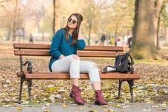 Скамейка в парке осени черной шляпы джинсов молодого красивого девочка-подростка сидя усмехаясь сорванная Стоковое фото RF