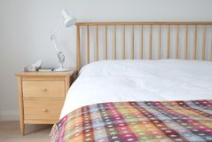 Скандинавский воодушевленный интерьер спальни показывая деревянную мебель спальни, белизну покрасил стены, белые постельные прина Стоковая Фотография RF