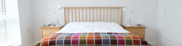 Скандинавский воодушевленный интерьер спальни показывая деревянную мебель спальни, белизну покрасил стены, белые постельные прина Стоковое фото RF