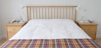 Скандинавский воодушевленный интерьер спальни показывая деревянную мебель спальни, белизну покрасил стены, белые постельные прина Стоковая Фотография