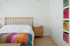 Скандинавский воодушевленный интерьер спальни показывая деревянную мебель спальни, белизну покрасил стены, белые постельные прина Стоковое Фото