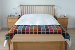 Скандинавский воодушевленный интерьер спальни показывая деревянную мебель спальни, белизну покрасил стены, белые постельные прина Стоковые Изображения