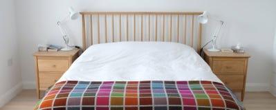 Скандинавский воодушевленный интерьер спальни показывая деревянную мебель спальни, белизну покрасил стены, белые постельные прина Стоковые Фото
