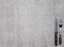 Скатерть от грубой linen ткани с вилкой и ножом Творческая предпосылка для знамени или кафа или ресторана меню Стоковые Фото