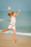 Скача девушка летая пляжа на голубом береге моря стоковое фото