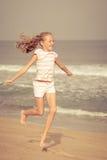 Скача девушка летая пляжа на голубом береге моря стоковое изображение