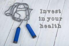 скача/прыгая веревочка с голубыми ручками на белой деревянной предпосылке с текстом инвестирует в вашем здоровье стоковые фотографии rf