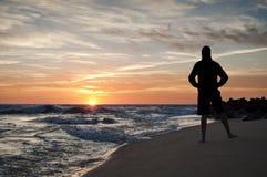 Скача силуэт человека на пляже на заходе солнца Стоковые Фотографии RF